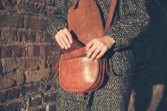 Frau bei dem Sonnenuntergang, der Geldbörse von der Tasche erhält Stockfoto