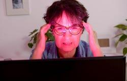Frau bei der Arbeit mit dem Computer, der schmerzliche Kopfschmerzen erleidet Lizenzfreies Stockbild