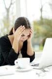 Frau bei Tisch gesessen mit Kopf in den Händen Lizenzfreie Stockfotos