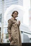 Frau am beige Mantel auf Treppe mit Regenschirm lizenzfreie stockfotos
