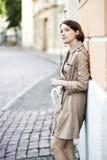 Frau am beige Mantel beobachten Aktionen auf Straße stockfoto