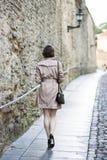 Frau am beige Mantel geht entlang die Wand stockfoto