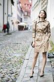 Frau am beige Mantel mit der Handtasche, die oben schaut stockfotos