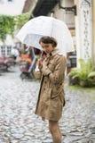 Frau am beige Mantel mit Regenschirm glaubt Kälte stockbilder