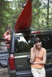 Frau beim Anruf als Mann-Bindungs-Kajak auf Auto-Dach stockbilder