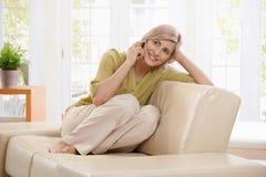 Frau beim Anruf auf Sofa Stockfoto