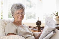 Frau beim Wohnzimmerlesezeitungslächeln stockbild