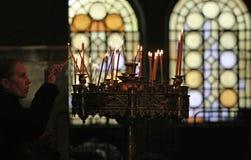 Frau beleuchtet eine Kerze Stockfotografie