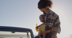 Frau bemannt an den Schoss, der auf einem Kleintransporter am Strand 4k sitzt stock video footage