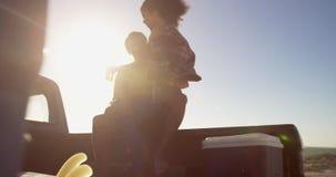 Frau bemannt an den Schoss, der auf einem Kleintransporter am Strand 4k sitzt stock footage