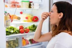 Frau bemerkte Geruch in Front Of Refrigerator stockbilder