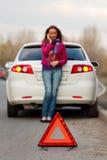 Frau benennt zu einem Service, der ein weißes Auto bereitsteht. Lizenzfreie Stockbilder