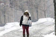 Frau benutzt cel-Telefon im Schneesturm Stockfotos