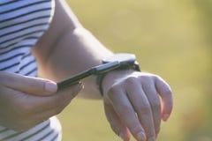 Frau benutzt das smartwatch und das intelligente Telefon stockbilder