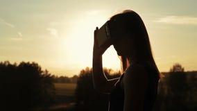 Frau benutzt Gläser einer virtuellen Realität im Wald bei Sonnenuntergang stock footage