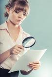 Frau benutzt Lupe, um Vertrag zu überprüfen stockfotografie