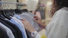 Frau berührt Aufhänger mit T-Shirts im Ausstellungsraum, Nahaufnahme von Händen stock video footage