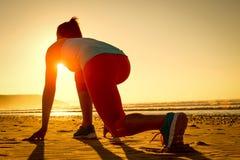 Frau bereit zum Laufen auf Sonnenuntergangstrand Lizenzfreies Stockbild