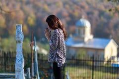 Frau betet vor einem Kreuz im cemeter Stockbild