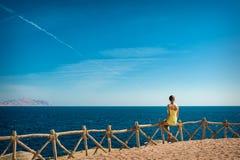 Frau betrachtet das Meer und die Insel von Tiran lizenzfreies stockbild