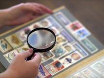 Frau betrachtet durch Kennzeichen eines Vergrößerungsglasalbums stockbild