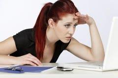 Frau betroffen bei der Arbeit Stockbild