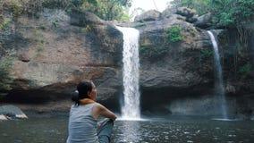 Frau bewundert den schönen Wasserfall stock video