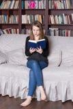 Frau am Bibliothekslesebuch Lizenzfreie Stockfotos