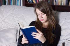 Frau am Bibliothekslesebuch Lizenzfreie Stockfotografie