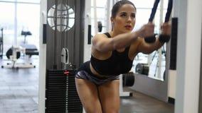 Frau bildet Arme und Schultern auf Simulator in der Turnhalle aus stock footage