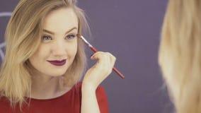 Frau bildet ihre Augen vor Spiegel stock video footage