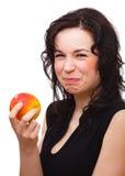 Frau bildet saures Gesicht, nachdem sie einen Apfel gebissen hat stockbilder