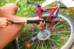 Frau bläst einen Reifen ihres Fahrrades auf lizenzfreies stockfoto