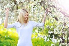 Frau in blühendem Baum im Frühjahr Lizenzfreies Stockfoto