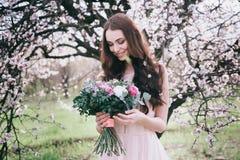 Frau in blühenden Bäumen Frau mit Hochzeitsblumenstrauß in den Händen Stockfotografie