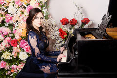 Frau blauen Kleid der Spitzes im tief, welches das Klavier und die Blumen spielt Retro- Abbildung der Weinlese style Stockfotos