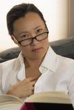 Frau blickt oben von ihrem Buch flüchtig Lizenzfreie Stockbilder