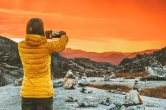 Frau Blogger, der Foto durch Smartphone von Sonnenuntergangbergen macht Stockfotografie