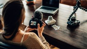 Frau Blogger, der ihre Kamera betrachtet Stockfoto