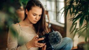 Frau Blogger, der ihre Kamera betrachtet Stockfotografie
