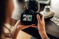 Frau Blogger, der ihre Kamera betrachtet Lizenzfreies Stockbild