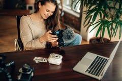 Frau Blogger, der ihre Kamera betrachtet Stockbilder