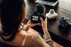 Frau Blogger, der ihre Kamera betrachtet Lizenzfreies Stockfoto