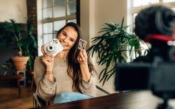 Frau Blogger, der ihren Inhalt auf Kamera notiert Stockfotos