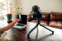 Frau Blogger, der ihren Inhalt auf Kamera notiert Stockbild