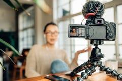 Frau Blogger, der ihren Inhalt auf Kamera notiert Stockbilder