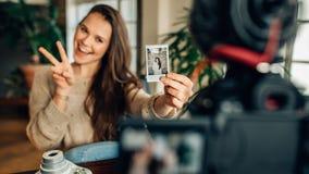 Frau Blogger, der ihren Inhalt auf Kamera notiert Lizenzfreie Stockbilder