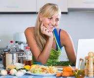 Frau blogging ungefähr kulinarisch vom Hauptnotizbuch Lizenzfreie Stockbilder