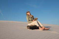 Frau, Blondine sitzt allein im Strand und plaudert mit Freunde usi Stockfotos