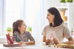 Frau bringt Kind das Alphabet bei stockbilder